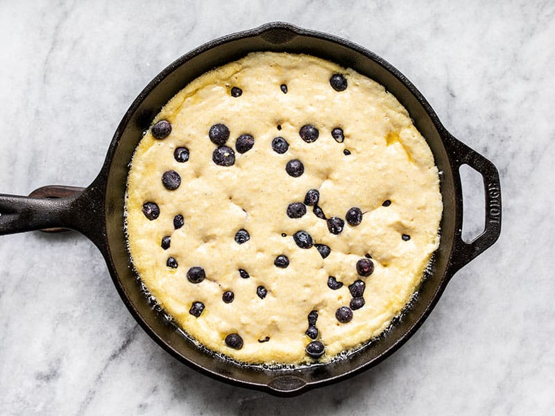 Batter and blueberries in hot skillet ready to bake.