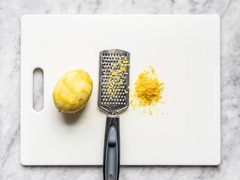 A zested lemon on a cutting board with a zester