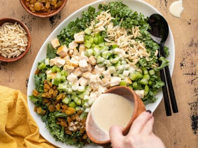 dressing being poured over kale and chicken salad
