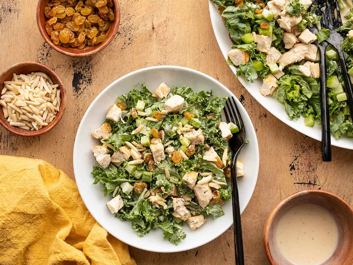 Tossed kale and chicken salad in a bowl next to the serving platter full of kale salad