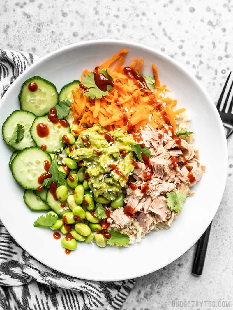 Overhead view of a Spicy Tuna Guacamole Bowl with sriracha and sesame seeds sprinkled over top.