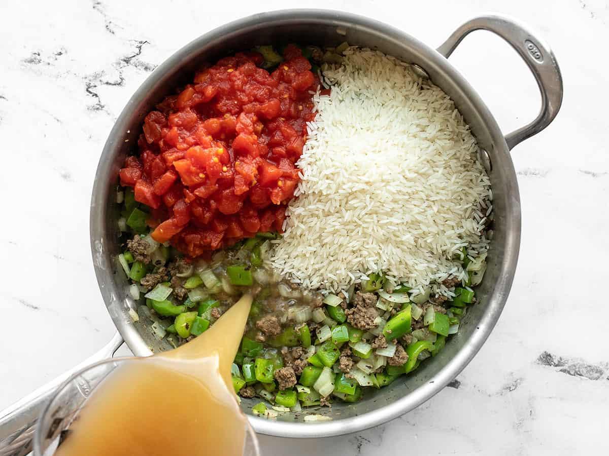 Tomates, arroz e caldo adicionados à frigideira.