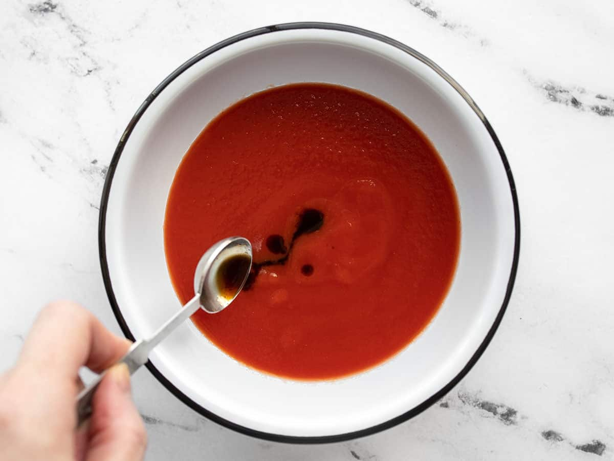 Worcestershire sauce being added to tomato sauce
