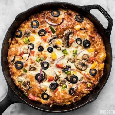 A simple overnight no knead dough makes a perfectly crispy yet thick crust on this no knead pan pizza. Deep dish pan pizza has never been easier. BudgetBytes.com