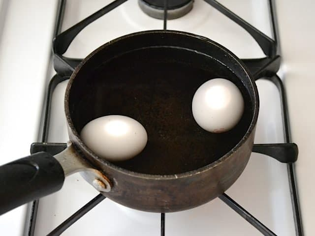 Two eggs boiling in pot of water on stove top