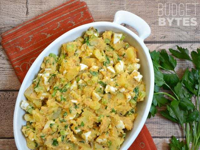 Top view of a dish of Cajun Potato Salad with parsley and an orange napkin on the side