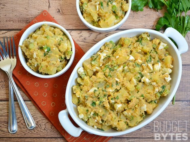 Cajun Potato Salad in casserole dish with two small bowls served out and two forks