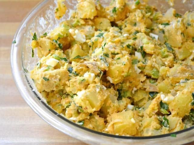 Potatoes and dressing added to mixing bowl with eggs and veggies