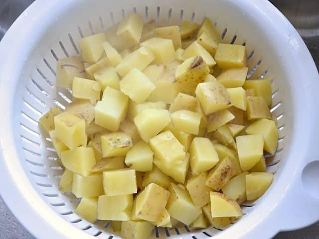 Cooked cubed potatoes in colander draining