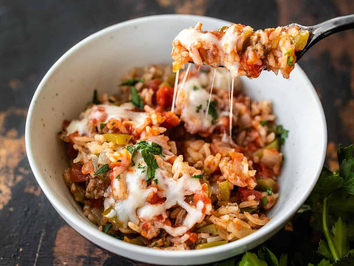Um garfo tirando um pouco de arroz e queijo de uma tigela de pimentões não recheados