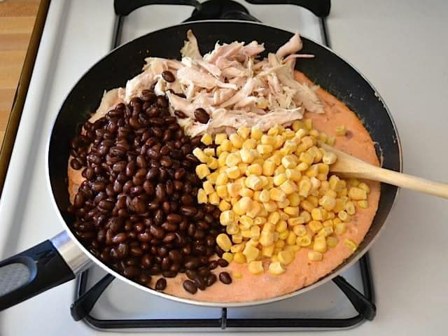 Shredded chicken, black beans and corn added to tomato sauce in skillet