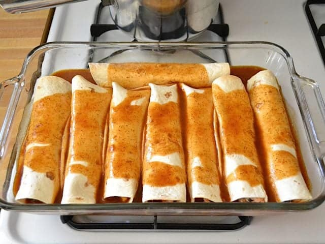 Enchilada sauce poured over rolled enchiladas in baking dish and ready to bake