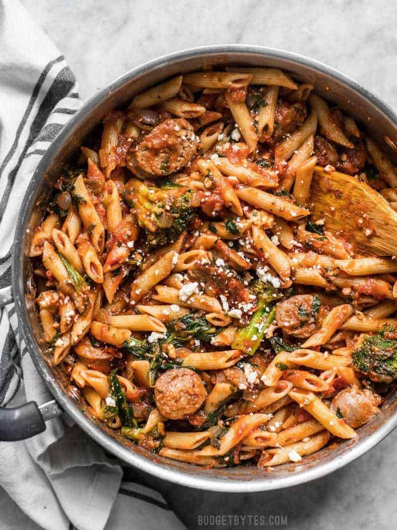A large pot full of Penne Pasta with Sausage and Greens with feta sprinkled over top and a wood spoon