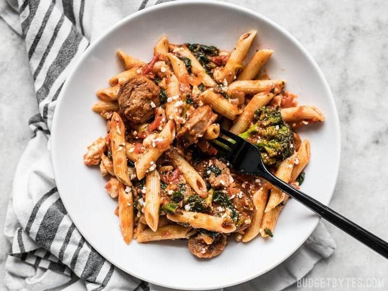 A plate full of Penne Pasta with sausage and greens