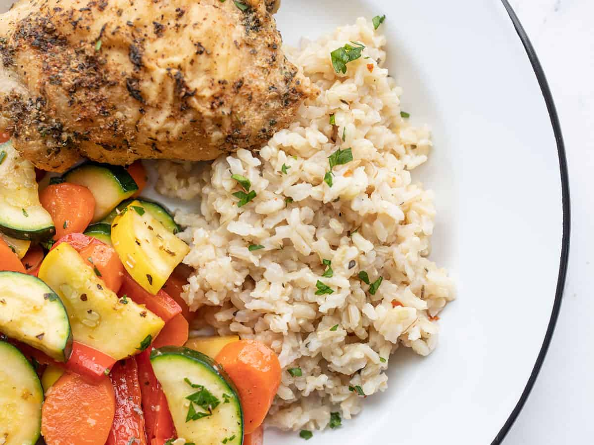 Seasoned rice on a plate with vegetables and chicken