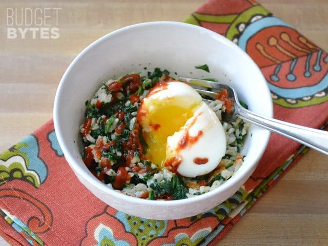 Soft boiled egg put on top of rice and spinach mixture in bowl