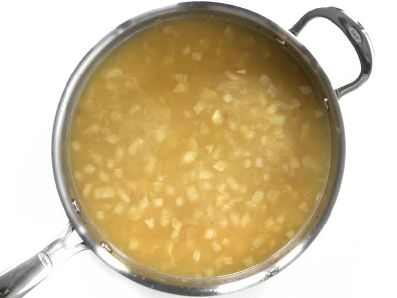 Chicken broth added to skillet with onions