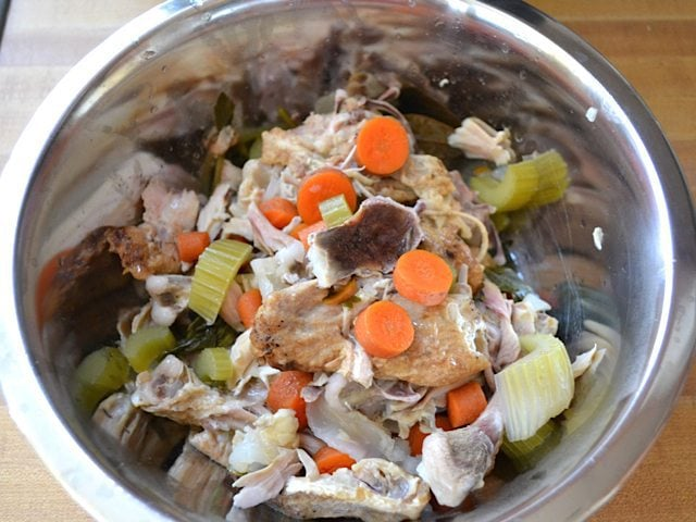 Large pieces of veggies and chicken taken out of slow cooker with slotted spoon