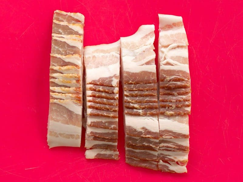 Sliced Bacon on red cutting board