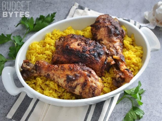 A bowl of Slow Cooker 5 Spice Chicken over a bed of rice, napkin and cilantro on the side for staging
