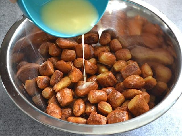 Pouring melted butter over cooked pretzel bites in mixing bowl
