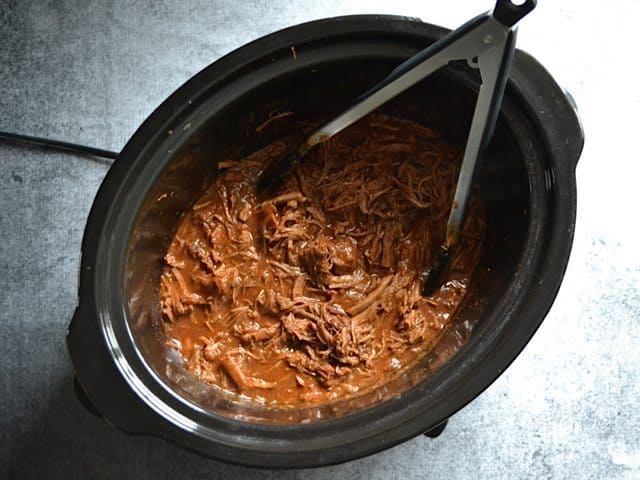 Shredding the Southwest Beef in slow cooker with tongs