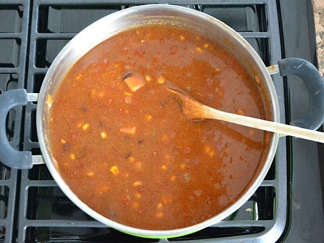 Tortilla Soup simmering in pot on stove top, stirred with wooden spoon