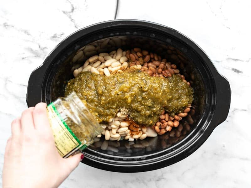 Salsa verde being poured into the slow cooker
