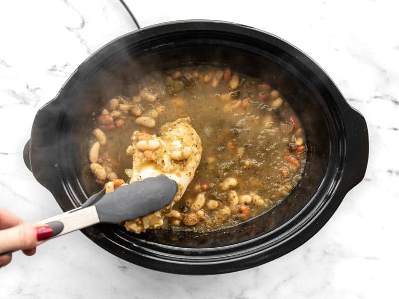 Chicken breast being removed from slow cooker with tongs