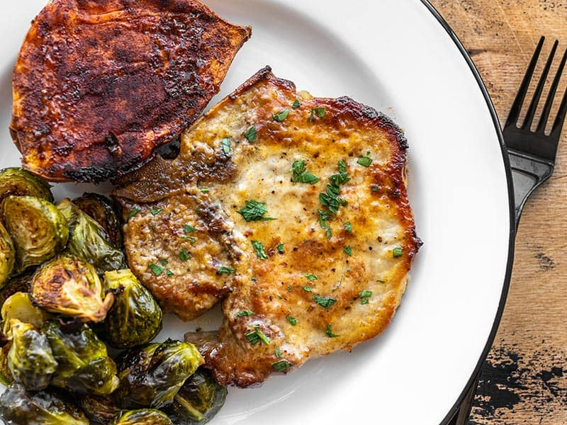 Honey mustard pork chop on a plate with brussels sprouts and sweet potato