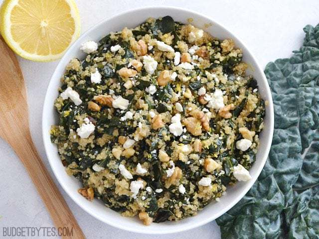 Top view of a bowl of Lemony Kale and Quinoa Salad with a wooden spoon and a half a lemon on the side