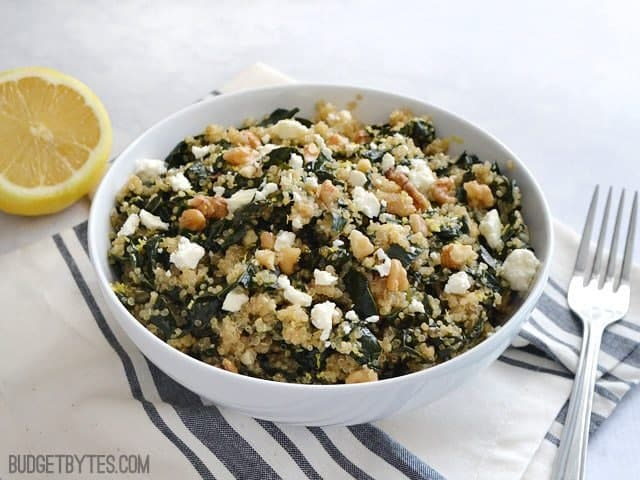 Side view of a bowl of Lemony Kale and Quinoa Salad sitting on a gray and white stripped napkin with a fork and half a lemon on the side