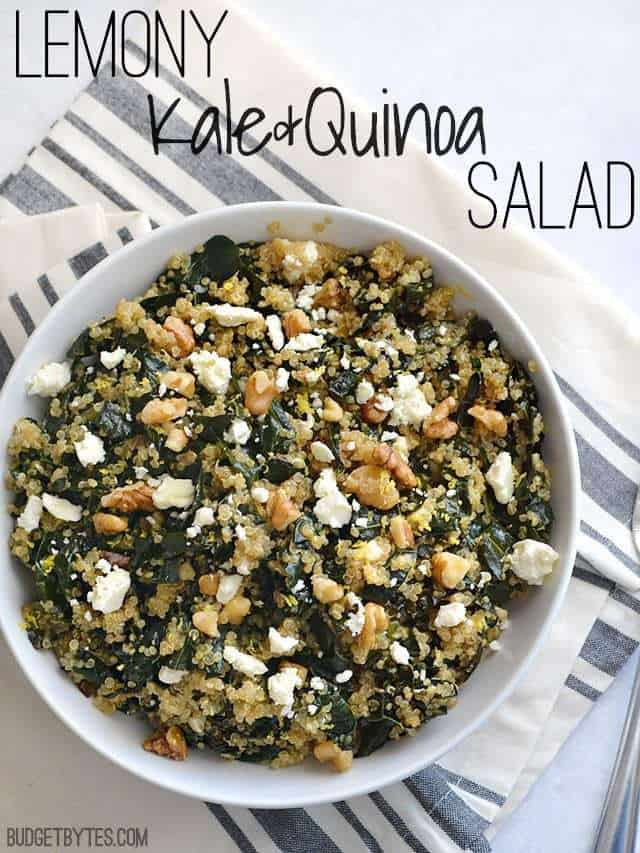 Top view of a bowl of Lemony Kale and Quinoa Salad sitting on a gray and white stripped napkin