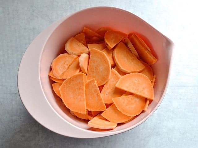 Peeled and Sliced Sweet Potatoes in pink mixing bowl