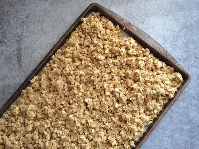 Granola spread out on baking sheet ready to bake