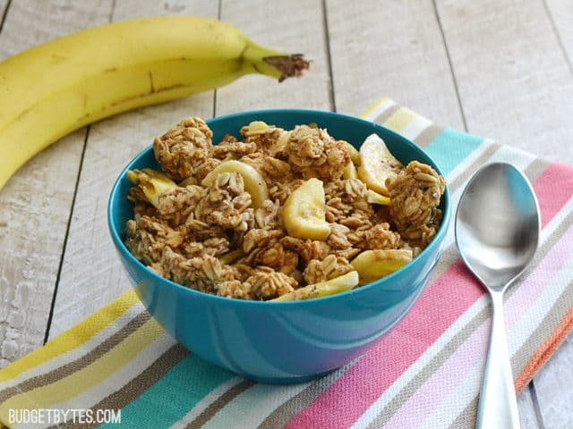 Side view of a bowl of Banana Nut Granola sitting on a colorful napkin, whole banana and spoon on the side