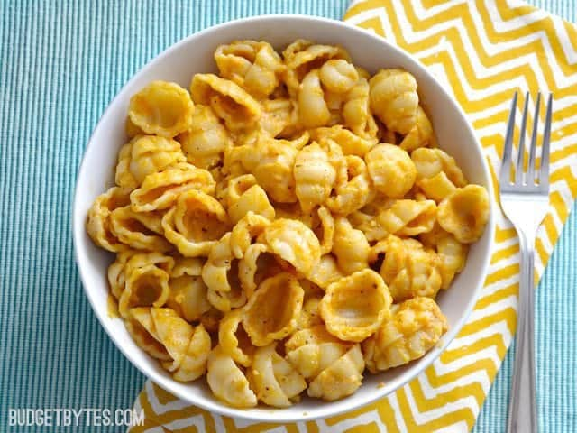 Top view of a bowl of Pasta with Creamy Pumpkin Sauce, sitting on a yellow chevron napkin with a fork on the side