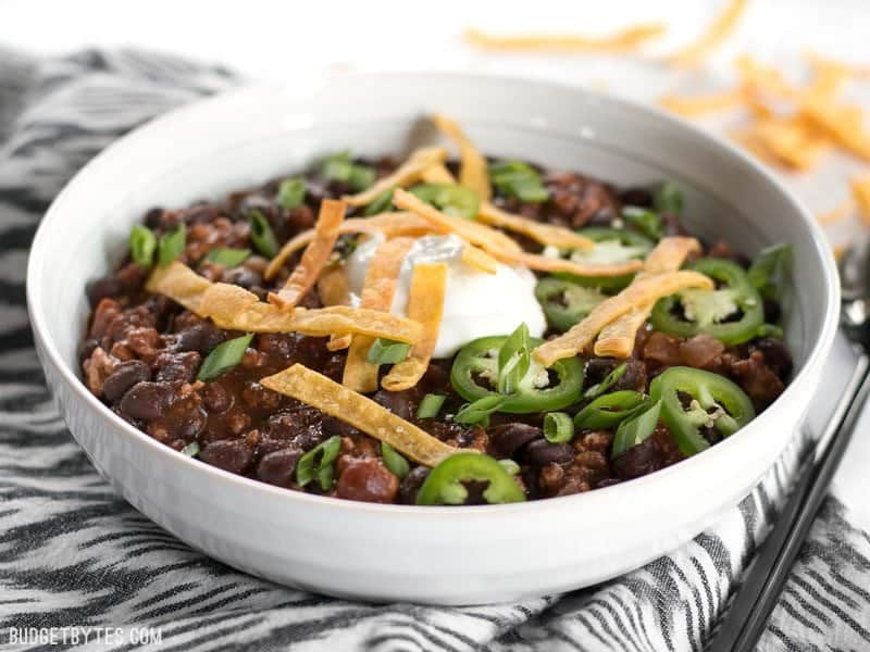 Front view of a bowl of Weeknight Black Bean Chili with sour cream, Jalapeños, tortilla strips.