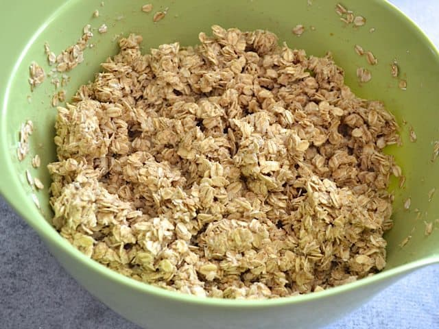 Banana sauce poured over granola mixture in mixing bowl