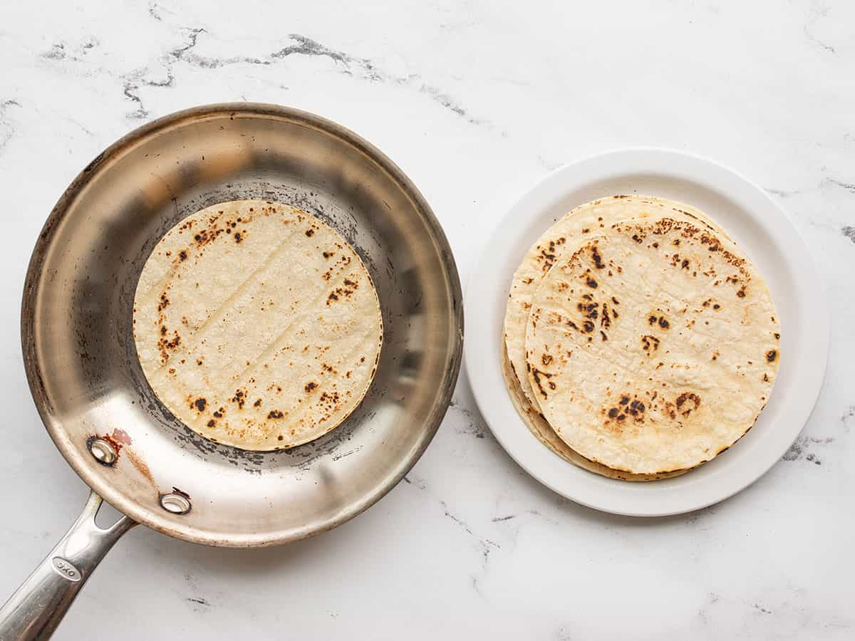 corn tortillas being toasted in a skillet
