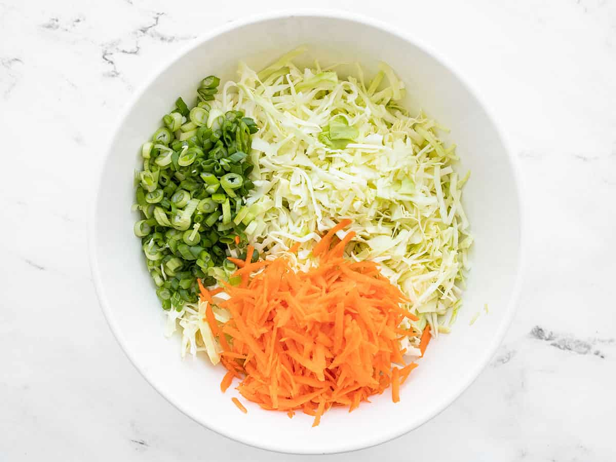 Shredded cabbage, carrots, and sliced green onion in a bowl