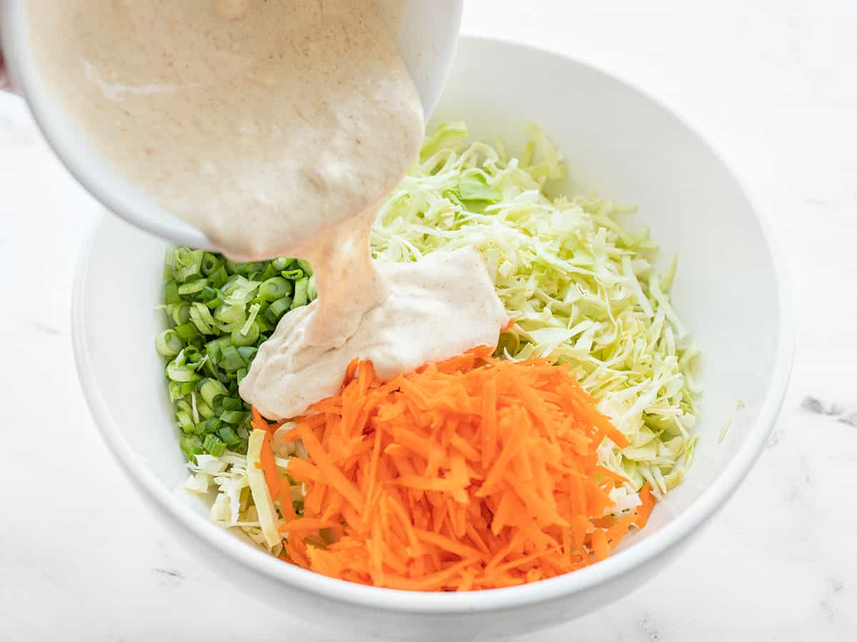 coleslaw dressing being poured over the vegetables in the bowl