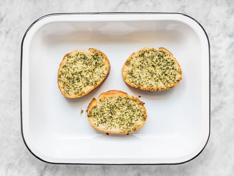 three garlic bread slices in a baking dish, baked