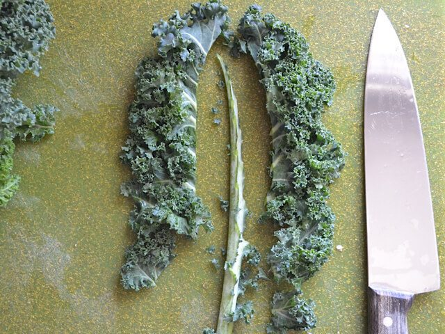 Removing the stems from kale with knife