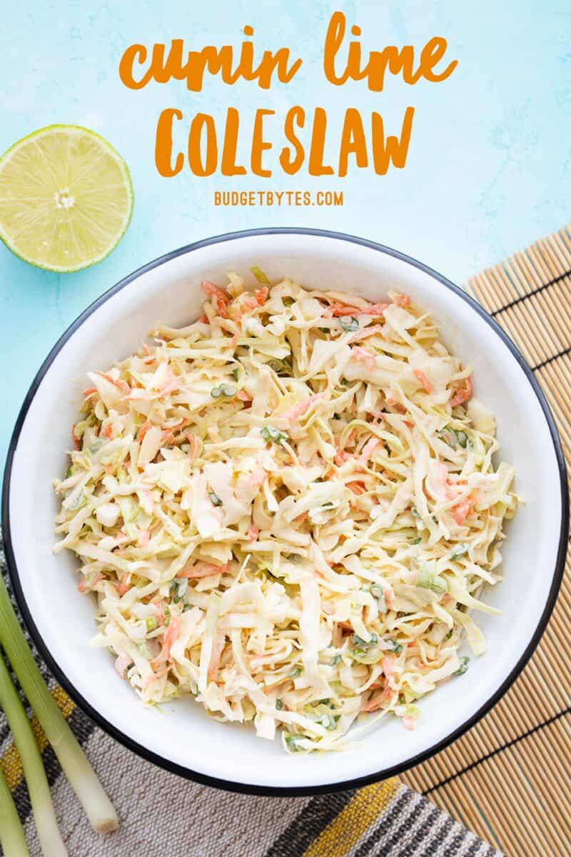 Overhead view of a bowl of cumin lime coleslaw with limes and green onion on the side
