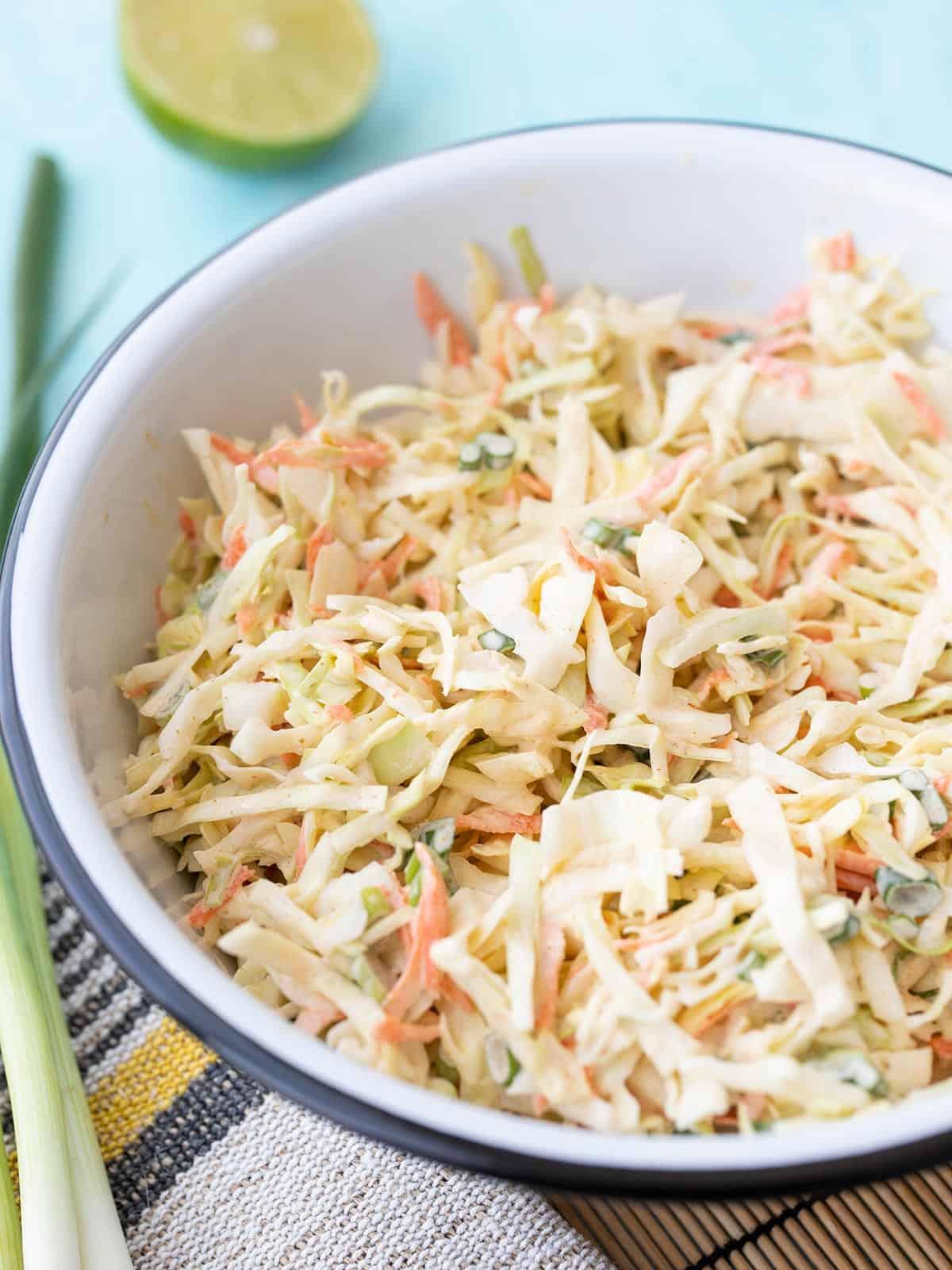 vista lateral de uma tigela de salada de repolho de limão com cominho com cebola verde e limão ao lado