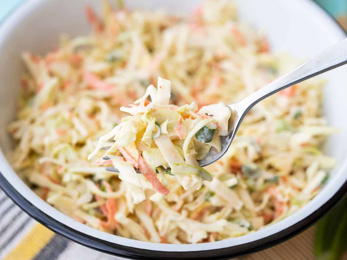 Closeup of a forkful of cumin lime coleslaw with the bowl in the background