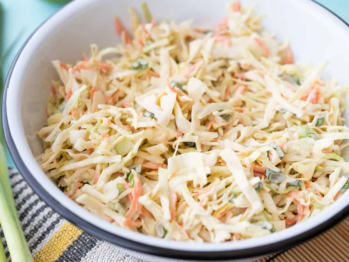 Side view of a bowl full of cumin lime coleslaw