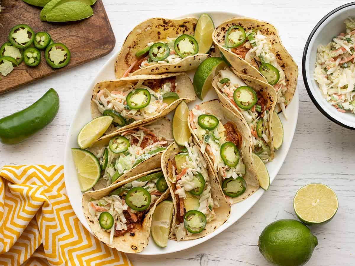 Fish tacos on a platter with toppings on the sides