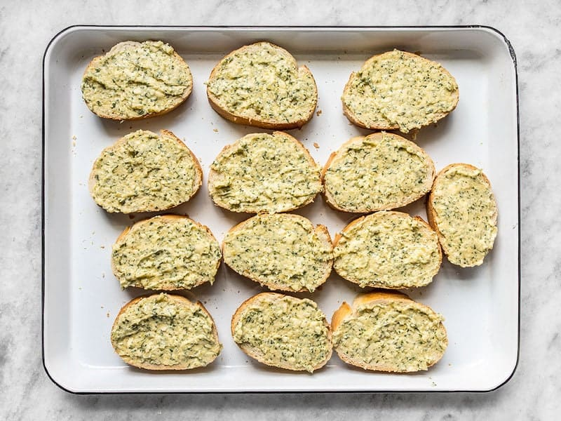 Garlic Spread on Bread Slices, on a baking sheet